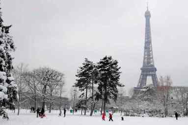 TOPSHOT - Children play in the snow covered Champ de Mars near the Eiffel tower, on February 7, 2018 in Paris, following heavy snowfall. Exceptionally heavy snowfall brought public transport in Paris and surrounding regions to a near halt on February 7, spelling misery for commuters after hundreds were forced to abandon their cars to sleep in emergency shelters overnight. / AFP / Thomas SAMSON