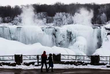 A couple looks out over the partially frozen American side of the Niagara Falls during sub-freezing temperatures in Niagara Falls, Ontario March 3, 2014. REUTERS/Mark Blinch (CANADA - Tags: ENVIRONMENT TRAVEL SOCIETY) ORG XMIT: MDB14