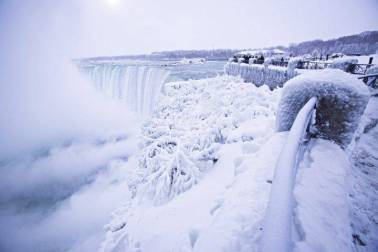 Visitors take photographs at the brink of the Horseshoe Falls in Niagara Falls, Ont., as cold weather continues through much of the province on Friday, Dec. 29, 2017.
