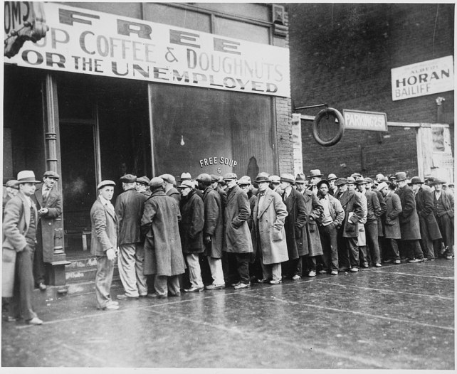 1024px-Unemployed_men_queued_outside_a_depression_soup_kitchen_opened_in_Chicago_by_Al_Capone,_02-1931_-_NARA_-_541927